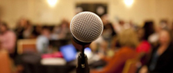 A photo of a microphone in the middle of a group meeting.