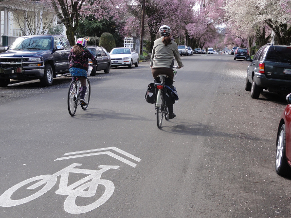 Photo of a woman and girl riding their bikes on a bicycle boulevard.