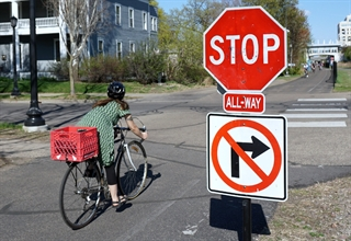 Woman cyclist stopped at an intersection at the stop sign.
