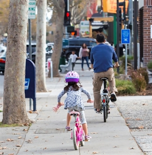 Imagine of young girl and her father riding on the sidewalk wearing a helmet.