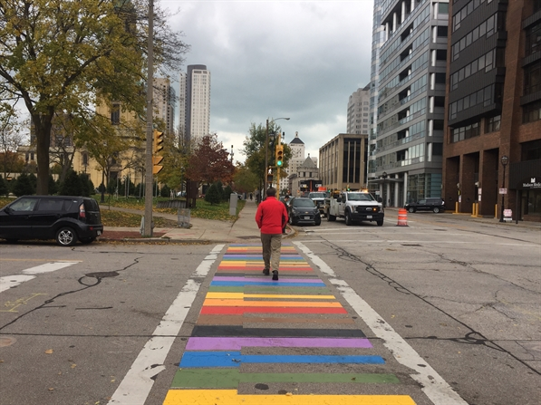 Photo of person walking in crosswalk painted with the colors of the rainbow in the shape of piano keys.