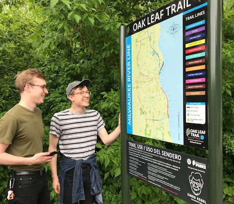 Two people looking at Oak Leaf Trail Sign