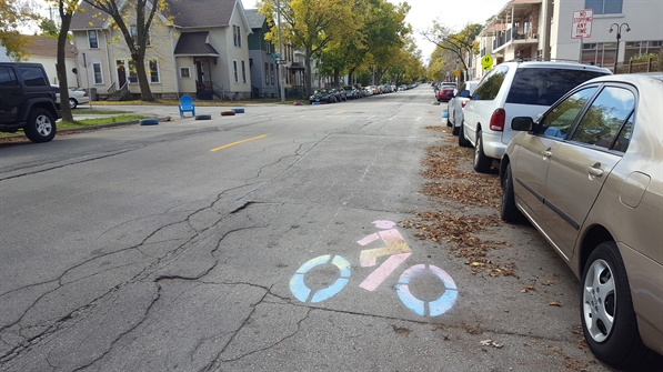 Photo of street with artistic, multicolor bike symbol