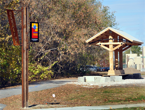 Image of the Beerline trail with signage and a pedestrian resting area.
