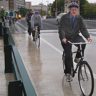 Mayor Barrett and others bicycling over Plankinton Bridge with bridge plating.