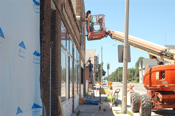 Workers fixing up a building on Vliet St.