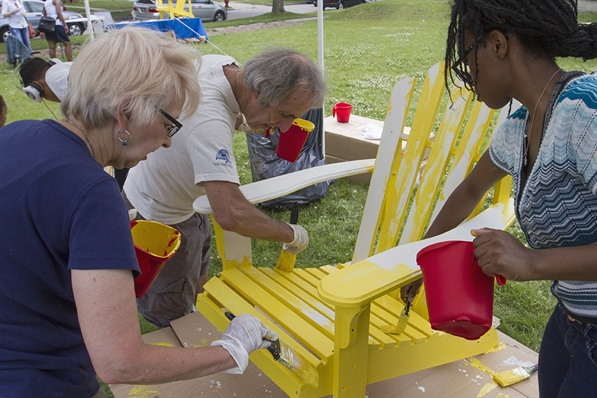 Image of neighbors painting a chair yellow