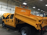 A photo of a yellow Department of Public Works Dump Truck
