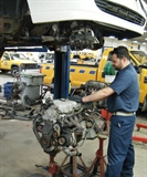 A photo of Zack Cronick working on a vehicle engine