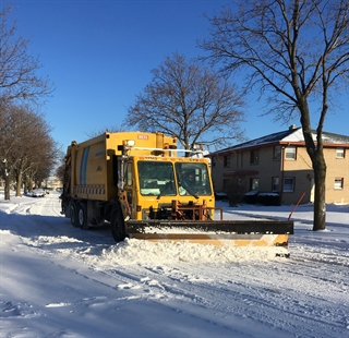 Garbage Packer with plow pushing snow