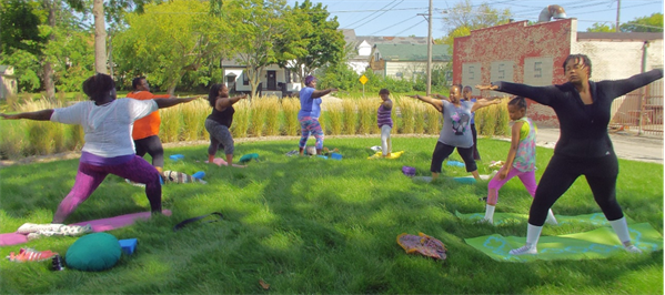 Community doing yoga in garden.