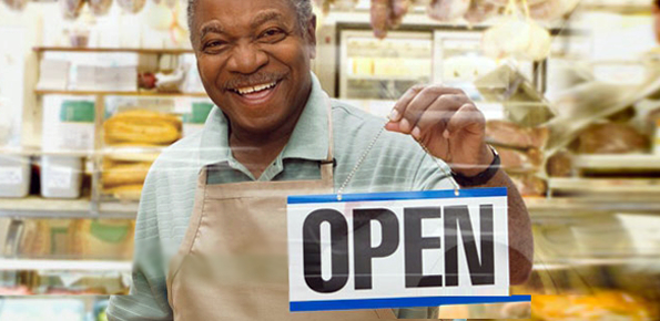 "Photo of business owner hanging an ""Open"" sign in his store window"