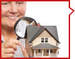 Photo of a woman looing at a model home with a magnifing glass