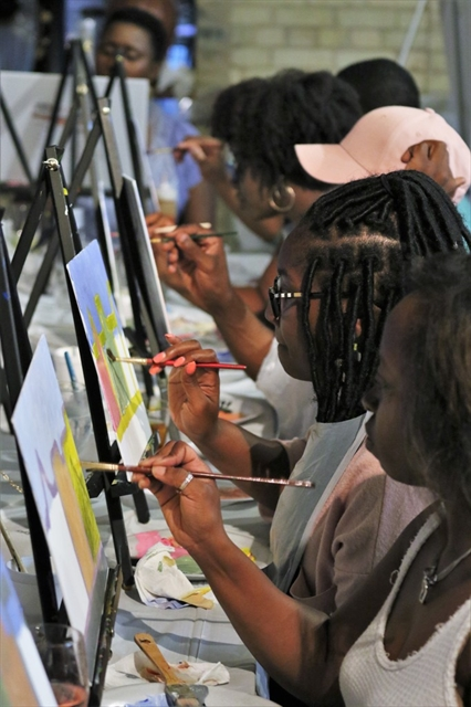 People painting at art event.