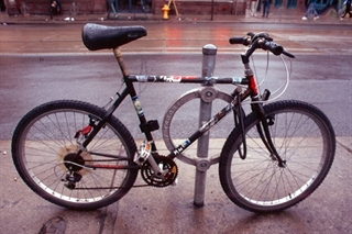 Image of a bicycle locked to a post and ring bike rack