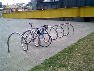 Bicycle locked to spiral bike rack in open public space