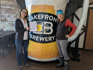 The manager of Lakefront Brewery shows off Lake Friendly Certification.
